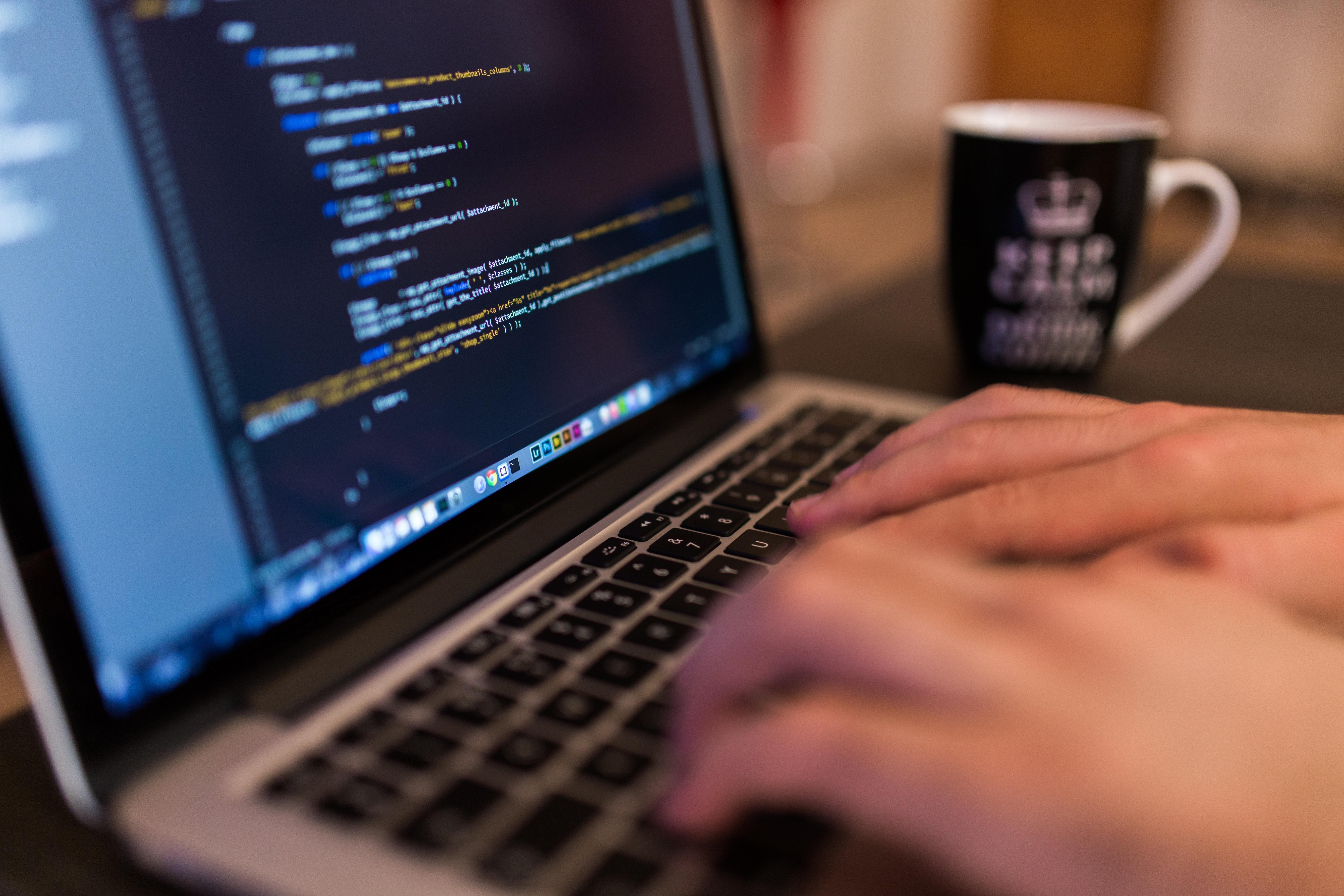Foto: Hände, die auf einer Tastatur tippen. Code auf dem Bildschirm. (Credit CC 0: Luis Llerena/Unsplash)